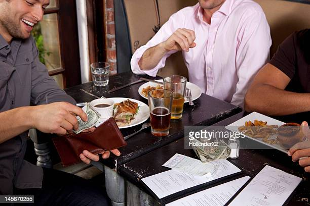 man paying check at dinner with friends
