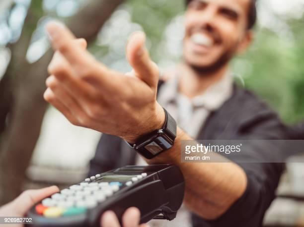 man betalen contactloos met smartwatch - wijzerplaat stockfoto's en -beelden