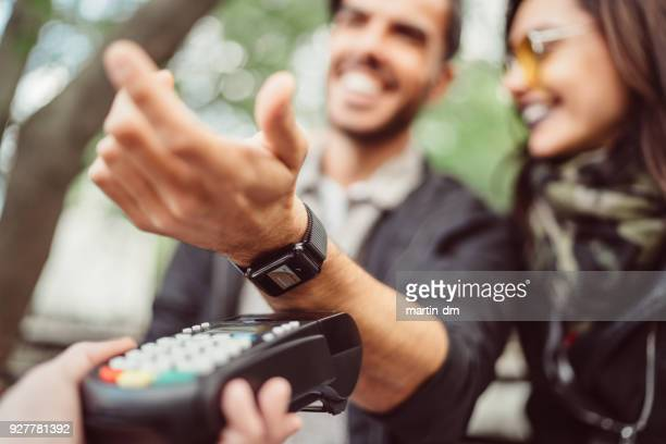 man paying contactless with smartwatch - smart watch stock pictures, royalty-free photos & images