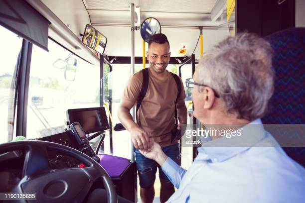 man paying fare to driver at entrance of bus - fare stock pictures, royalty-free photos & images