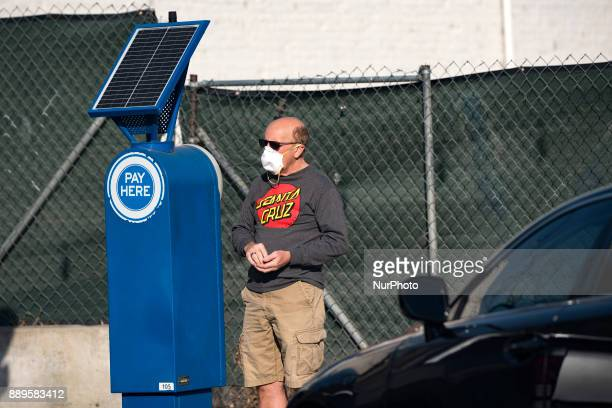 A man paying for a parking spot wears a face mask as protection from the heavy smoke as the Thomas wildfire burns in Ventura California on December 9...
