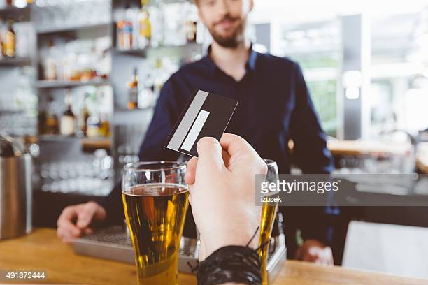 Man paying for beer by credit card in the pub