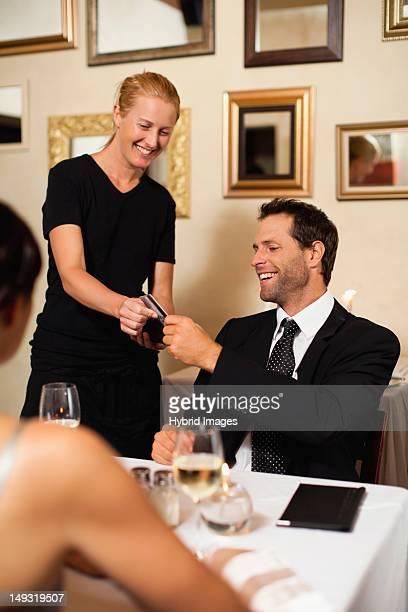 Man paying for dinner in restaurant