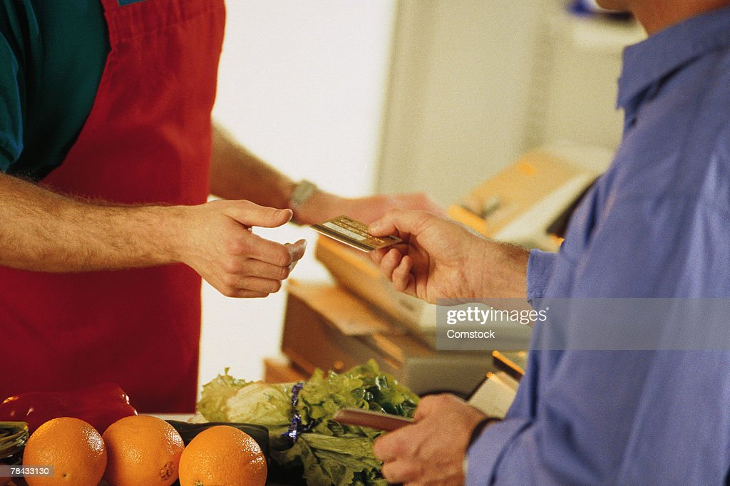 Man paying for groceries with credit card : Stock Photo