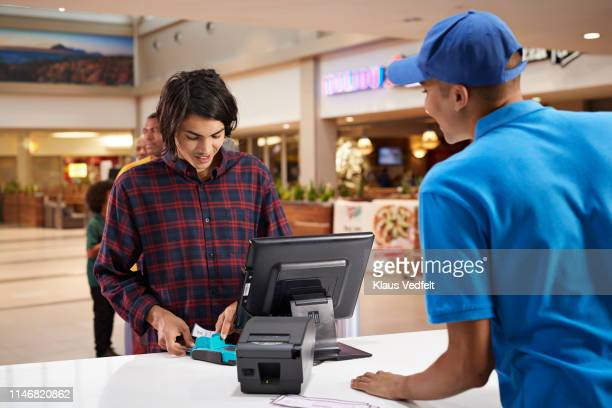 man paying for movie tickets at lobby - hygiaphone photos et images de collection