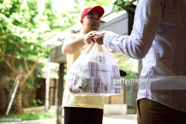 man paying for takeout food to delivery person using credit card reader - food delivery foto e immagini stock