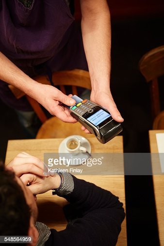 Man paying his bill in restaurant, using credit card, elevated view