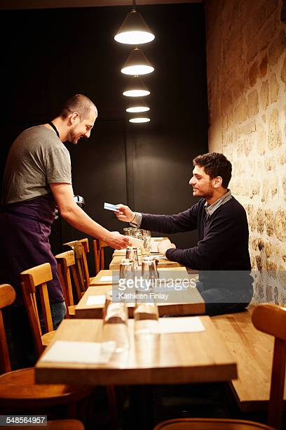 Man paying his bill in restaurant, using credit card