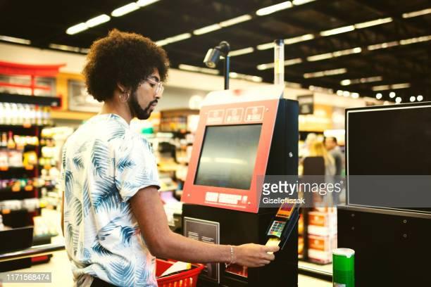 セルフサービスでスーパーマーケットで支払う男 - セルフサービス ストックフォトと画像