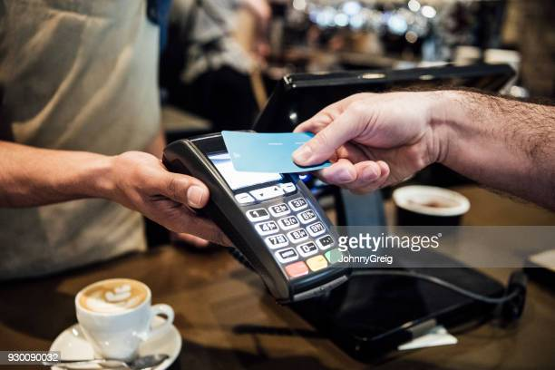 Man paying on card machine in cafe close up