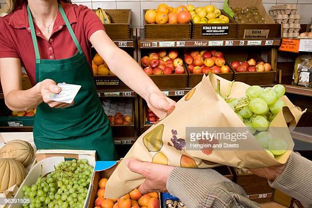 man paying shopkeeper for fruit