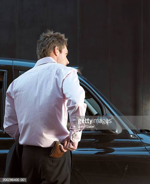 Man paying taxi fare, rear view.