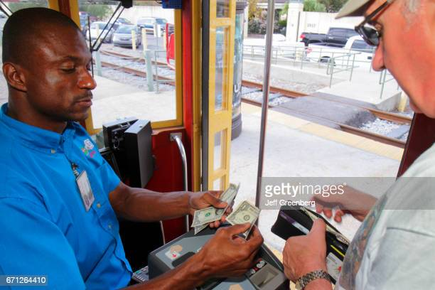 A man paying the conductor on the Riverfront Streetcar Line