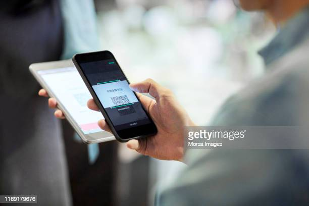 man paying through smart phone in cafe - contactless payment stock pictures, royalty-free photos & images