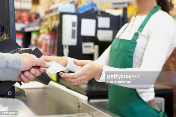 Man paying with credit card at grocery store