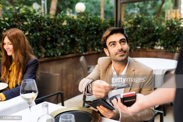 man paying with credit card in a restaurant - bezahlen stock-fotos und bilder