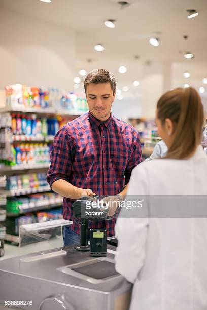 Man paying with smart phone in supermarket