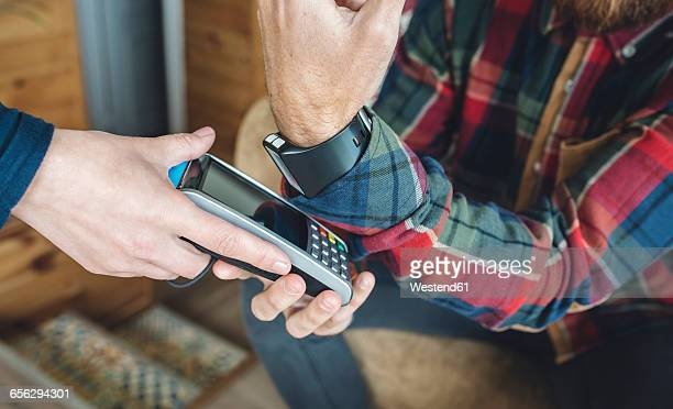 Man paying with smart watch in cafe