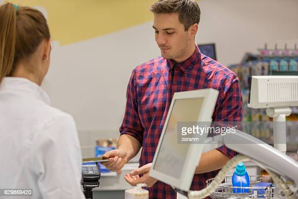Man paying with smartphone in supermarket