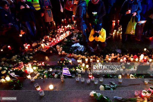 A man pays his respect at a memorial shift for the victims of the 2016 deadly truck attack at the Christmas market at Breitscheidplatz in front of...