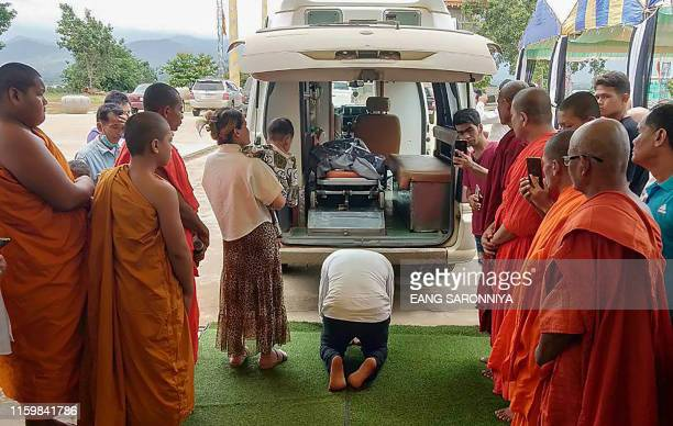 A man pays his respect during the arrival of the remains of former Khmer Rouge leader Brother Number Two Nuon Chea in a body bag transported by an...