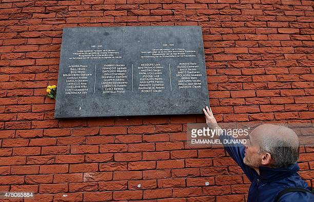 A man pays his respect touching a commemorative plaque bearing the names of the victims of the Heysel Stadium tragedy during a ceremony marking the...