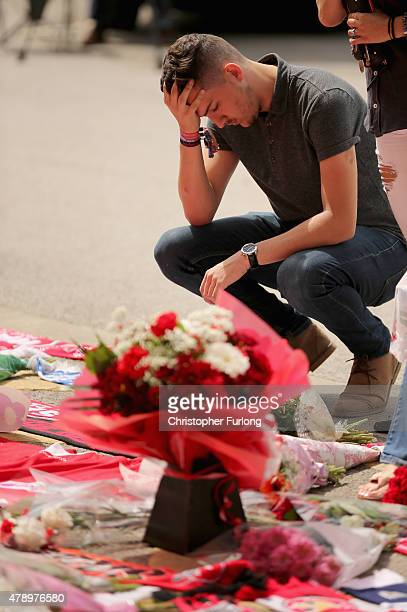 A man pays his respects as flowers and football tributes are laid outside Walsall Football Club in memory of Adrian Evans Patrick Evans and Joel...