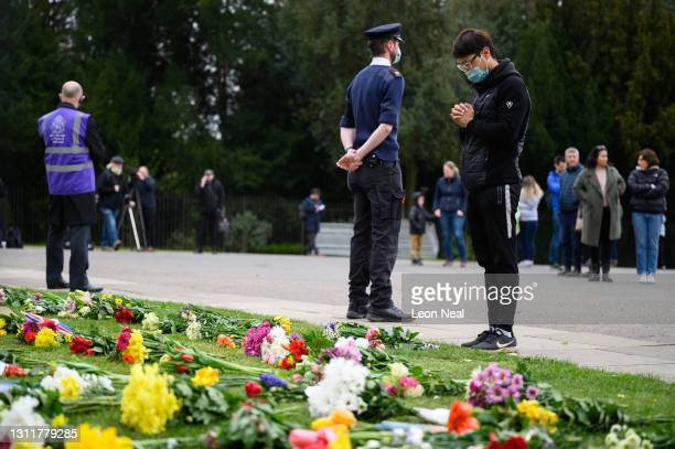 Man pays his respects as he looks at the floral tributes to Prince Philip, Duke Of Edinburgh who died at age 99, outside Windsor Castle on April 10,...