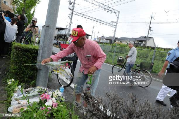A man pays his respects next to flowers and tributes laid at the scene where over 30 people died in a fire at an animation company building in Kyoto...
