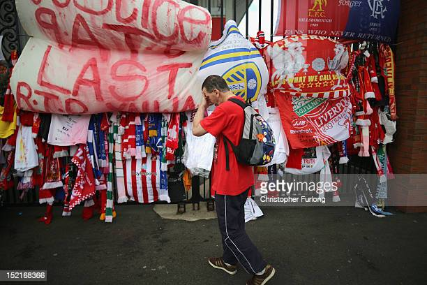 A man pays his respects next to tributes to the victims of the Hillsborough Disaster hanging on the Bill Shankly gates at Anfield Stadium on...