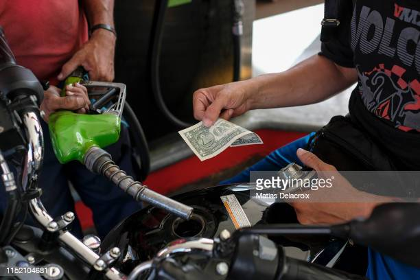 A man pays with a one US dollar bill after filling his motorbike tank at a gas station on June 26 2019 in Caracas Venezuela Everyday more Venezuelans...
