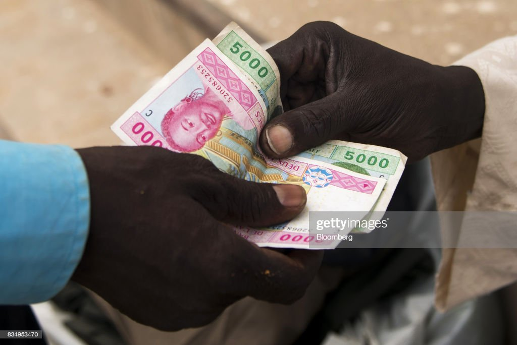 A man pays with a vendor with Central African franc banknotes on a street in N'Djamena, Chad, on Wednesday, Aug. 16, 2017. African Development Bank and nations signed agreement to finance a project linking the town of Ngouandere in Cameroon and Chads capital, NDjamena, according to statement handed to reporters in Cameroonian capital, Yaounde in July. Photographer: Xaume Olleros/Bloomberg via Getty Images