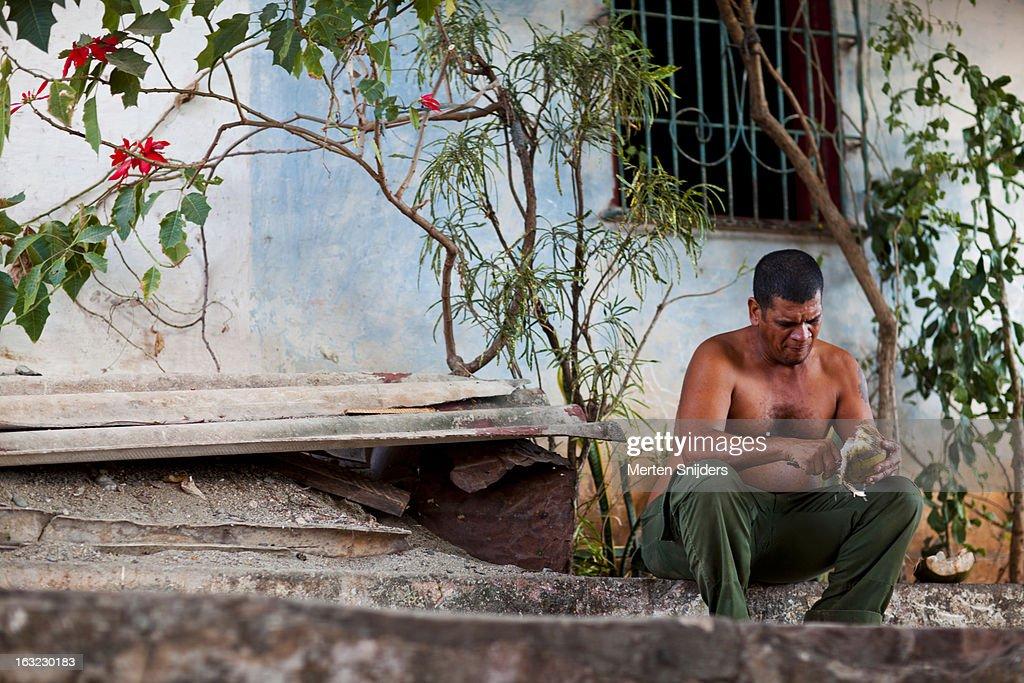 Man pealing coconut below flower bush : Photo