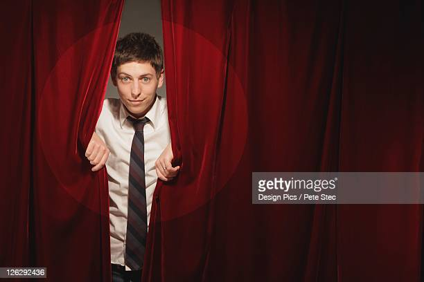 man peeking from behind red stage curtain