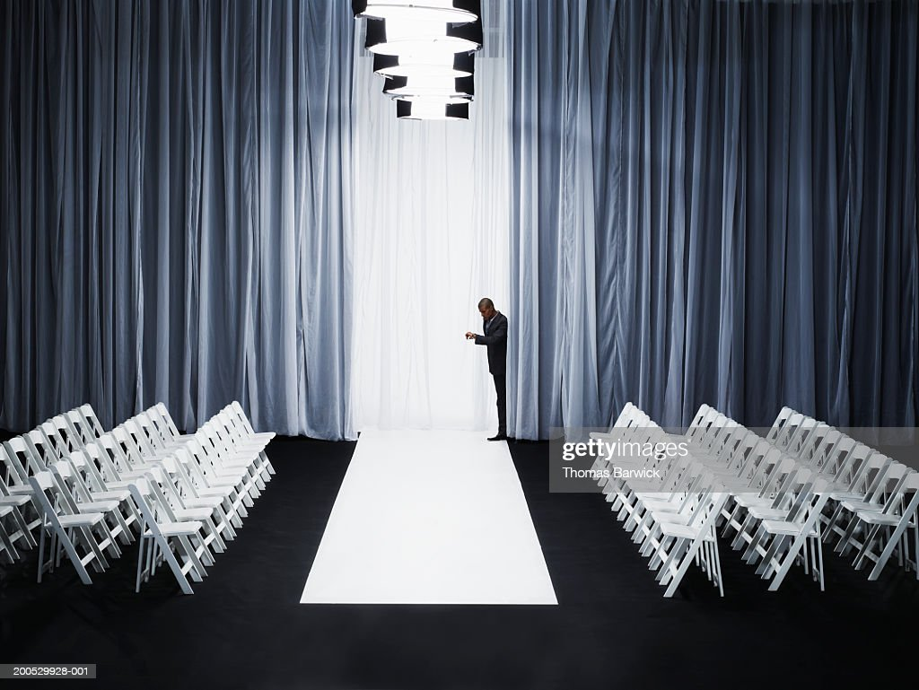 Man peeking out from behind curtain on catwalk, checking watch : Stock Photo