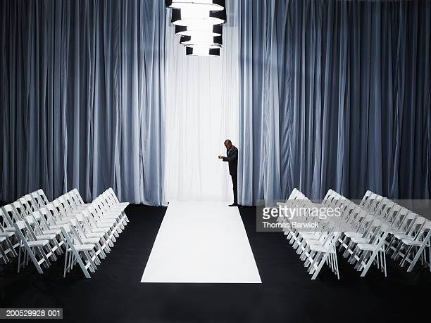 man peeking out from behind curtain on catwalk, checking watch - sfilata di moda foto e immagini stock