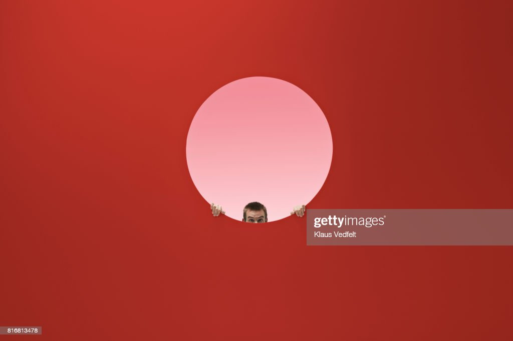Man peeking out of round opening in coloured wall : Stock Photo