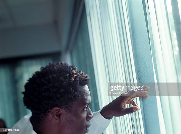 Man peeking out of window blinds
