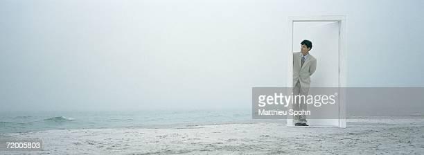 Man peeking through doorframe on beach