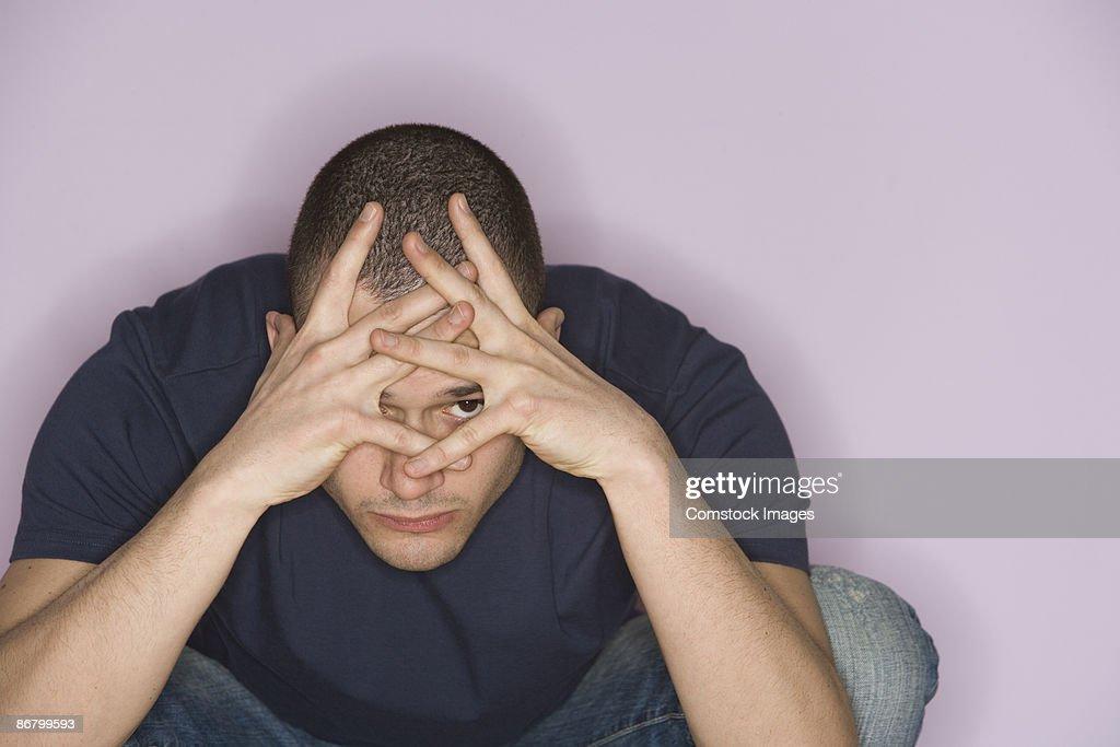 Man peeking through hands : Stock Photo