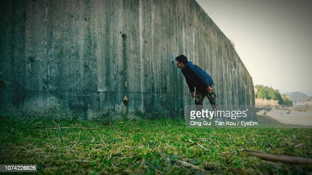 man peeking through hole of wall - peeping holes ストックフォトと画像