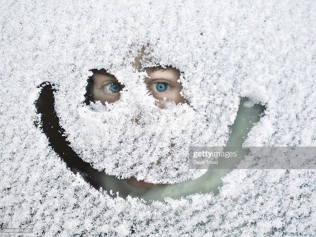 Man peeking through snow covered window : Stock Photo