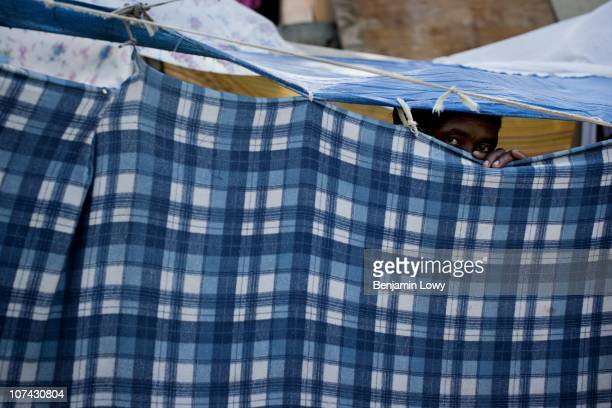 Man peeks from behind a tent made of tarps and sheets in the Champs des Mars IDP camp in Port au Prince on February 2 2010. Haiti was struck by a...