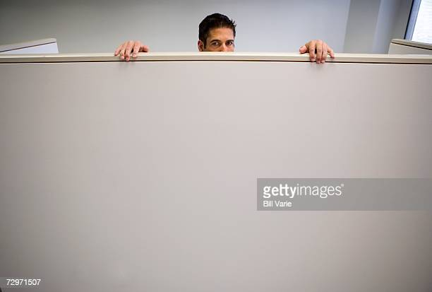 Man peeks over cubicle wall in an office