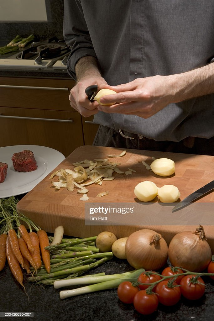 Man peelinig potatoes above cutting board in kitchen, close-up : Stock Photo