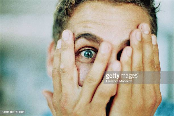 man peeping through fingers, portrait, close-up - peeking stock pictures, royalty-free photos & images