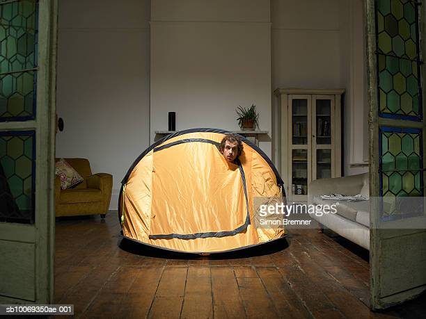 Man peering from tent in living room
