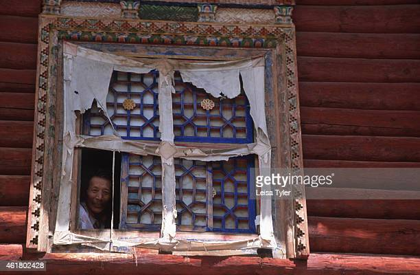 A man peering out of his living room window in Dege the former tibetan Kingdom of Kham Architecture specifically window eaves varies widely in Kham...
