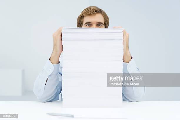 man peering over tall stack of paper - gender inequality stock photos and pictures