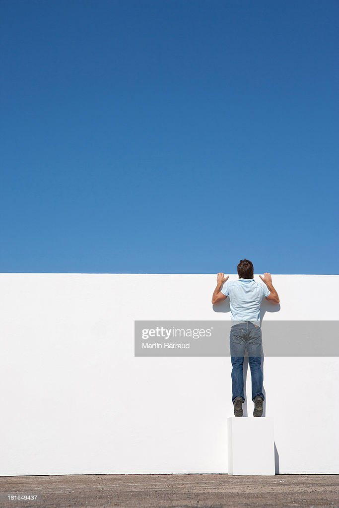 Man peering over wall outdoors with blue sky : Stock Photo